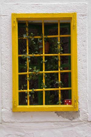 window bars: Window with yellow bars on Croatian coast Stock Photo