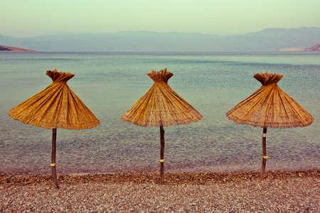 krk: three parasol on the coast of Krk  Croatia vintage style