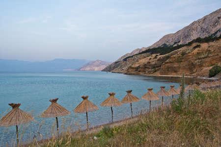 krk: parasol on the coast of isle Krk in Croatia Stock Photo