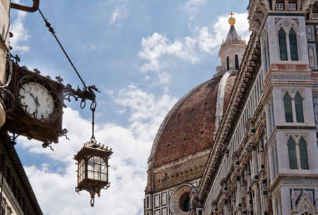 corner clock: Old clock with lantern in a corner of piazza duomo in Florence