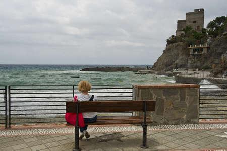 mare agitato: donna seduta su una panca di legno e guardando il mare mosso