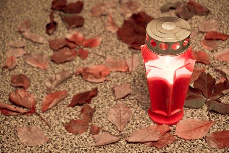 dode bladeren: Grave met licht kaarsen bij All Saints Day Stockfoto