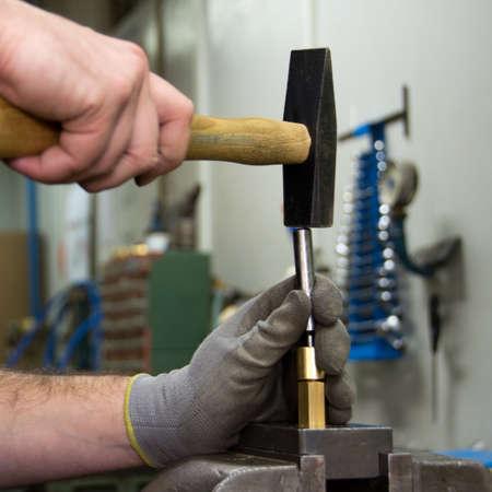 hammering: hammering in the mechanic workshop selective focus