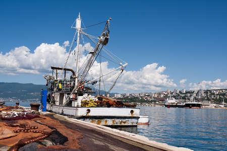 spread fishing nets, fishing boat on dock in port of Rijeka, Croatia