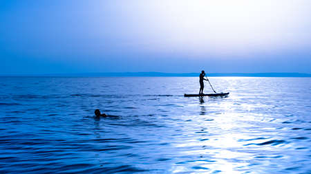 A surfer rowing on a surfboard Stock Photo