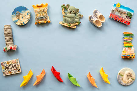 various souvenir magnets and paper ships arranged on the blue background
