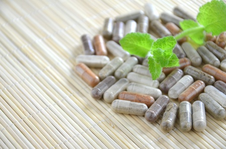 herbal capsules with mint leaves Stock Photo