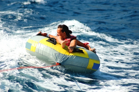 dashing: young girl dashing on tube on adriatic waters Stock Photo