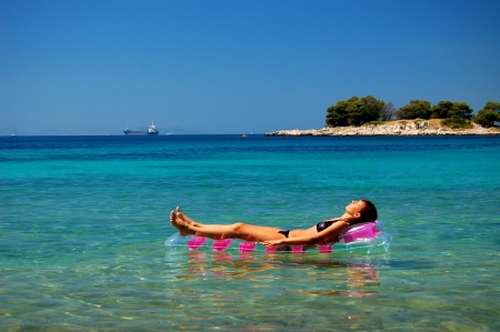 Gorgeous scenic view of young girl sunbathing on Adriatic waters in Croatia Stock Photo