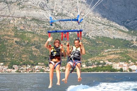 parasailing: Breathtaking view of two beautiful girls during parasailing