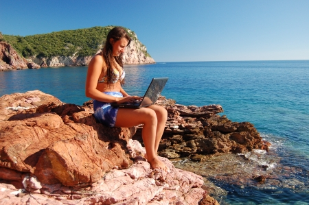 Attractive beautiful young girl using laptop on gorgeous picturesque rocky beach in Montenegro Stock Photo