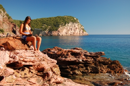 Attractive beautiful young girl using laptop on gorgeous picturesque rocky beach in Montenegro photo