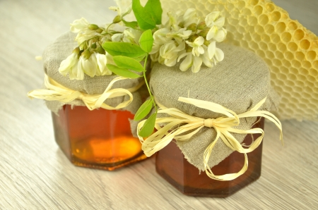 two jars of fresh delicious honey with honeycomb and acacia flowers photo