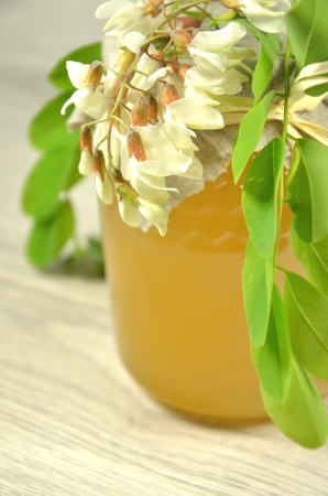 jar of fresh delicious honey with acacia flowers and honeycomb photo