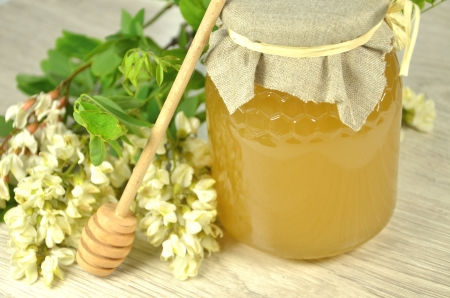 jar of fresh delicious honey with acacia flowers and honey dipper photo