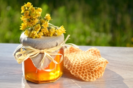 jar full of delicious fresh honey piece of honeycomb and wild flowers in apiary Stock Photo