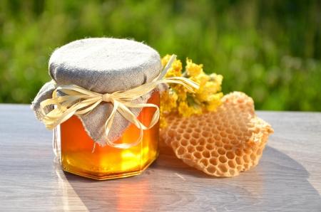 おいしい新鮮な蜂蜜の作品ハニカムと養蜂場で野生の花の完全な jar ファイルします。