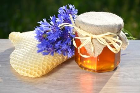 frasco: jarra llena de delicioso pedazo dulce miel de flores de nido de abeja y salvajes en colmenar