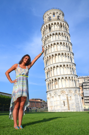 beautiful attractive brunette tourist girl holding leaning tower in pisa, italy Stock Photo