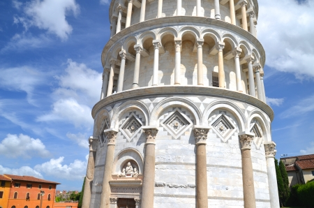 The famous Leaning Tower in Pisa on cloudy sky background photo