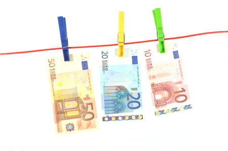 banconote essiccazione appesi sulla corda isolato su sfondo bianco