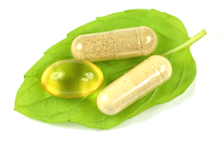 multivitamin: herbal capsules and fish oil capsule on mint leaf isolated on white  Stock Photo