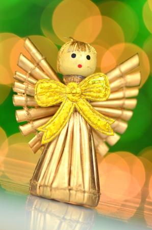 christmas decoration, golden angel made of straw against bokeh background photo