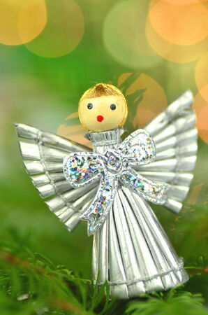 christmas decoration, silver angel made of straw and bokeh background photo