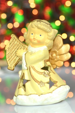 christmas decoration, figure of angel playing the harp against bokeh background photo