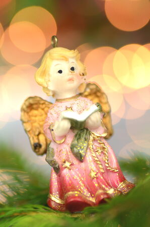 christmas decoration, figure of little angel singing carols against bokeh background photo
