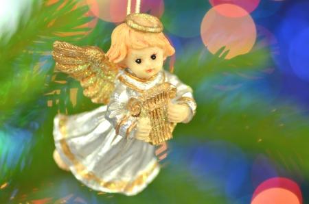 decorazioni natalizie, figura del piccolo angelo che suona l'arpa contro sfondo bokeh