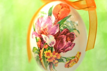 Easter egg decorated with flowers made by decoupage technique on green background photo