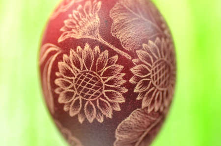 Traditional scratched handmade Easter egg on green background photo