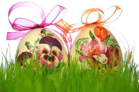 Easter eggs decorated with flowers made by decoupage technique in the grass photo