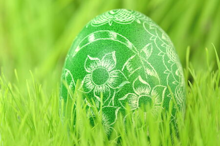traditional scratched handmade Easter egg in the grass photo