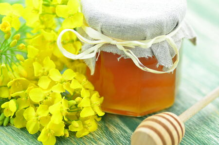 jar of delicious honey in a jar with rapeseed flowers and honey dipper
