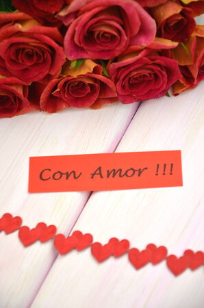 with love wishes in spanish and bouquet of gorgeous red roses photo