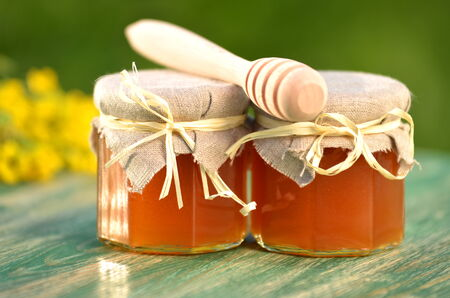 jar of delicious honey with rapeseed flowers and honey dipper photo