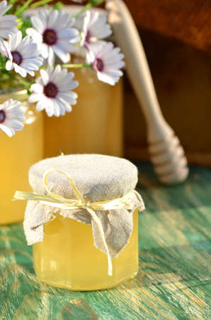 jars of delicious honey, flowers and honey dipper in apiary photo