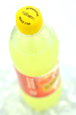 dewed: Bottle of Schweppes drink on ice cubes