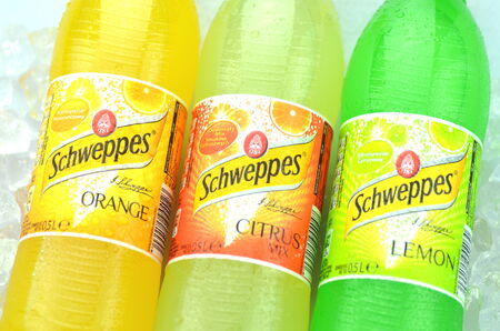 dewed: Bottles of Schweppes drink on ice cubes Editorial