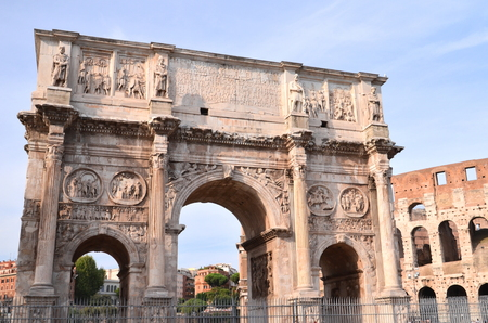 Triumphal Arch of Constantine and Colosseum in Rome against blue sky, Italy