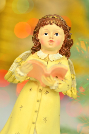 christmas decoration, figure of singing angel against bokeh background photo
