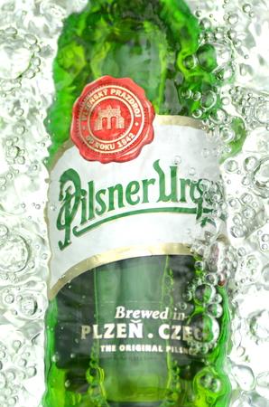 pilsner: Pilsner Urquell pale lager beer in splashed water. Editorial