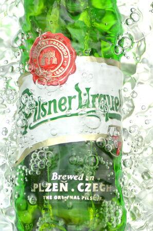 pilsner beer: Pilsner Urquell pale lager beer in splashed water. Editorial