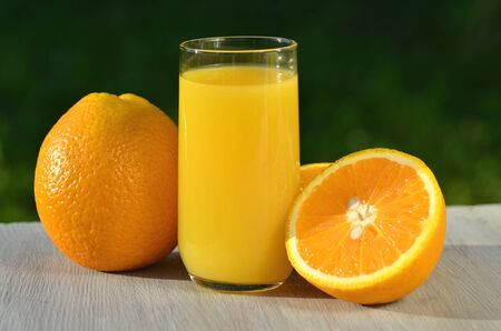 orange juice: glass of delicious orange juice and oranges on table in garden Stock Photo