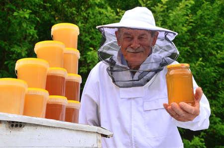 apiarist: Senior apiarist presenting a jar of fresh honey in apiary in the springtime Stock Photo