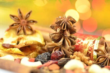 christmas scent: Christmas spices, nuts, cookies and dried fruits on bokeh background