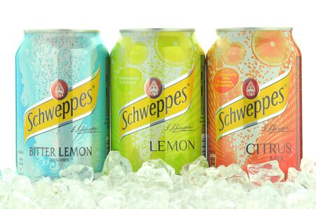 dewed: Cans of Schweppes drink on ice cubes Editorial