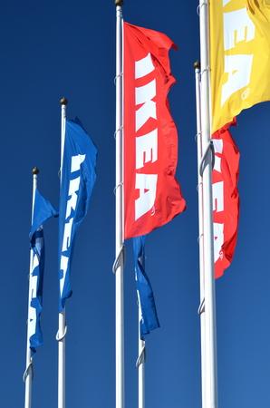 ikea: logo of ikea on waving flags against blue sky Editorial